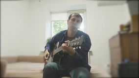 Όμορφος νέος μουσικός που παίζει την κιθάρα και το τραγούδι Άτομο που παίζει το ακουστικό σε αργή κίνηση βίντεο κιθάρων κοντά επά απόθεμα βίντεο