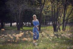 Όμορφος νέος ξανθός περίπατος γυναικών στο πάρκο Στοκ Εικόνα