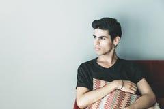 Όμορφος νέος στοχαστικός βραζιλιάνος τύπος με το μαξιλάρι στοκ εικόνες