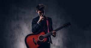 Όμορφος νέος στοχαστικός μουσικός με τη μοντέρνη τρίχα στα κομψά ενδύματα που θέτουν με μια κιθάρα στα χέρια του Στοκ φωτογραφίες με δικαίωμα ελεύθερης χρήσης