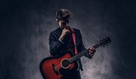 Όμορφος νέος στοχαστικός μουσικός με τη μοντέρνη τρίχα στα κομψά ενδύματα που θέτουν με μια κιθάρα στα χέρια του Στοκ Εικόνα
