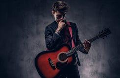 Όμορφος νέος στοχαστικός μουσικός με τη μοντέρνη τρίχα στα κομψά ενδύματα που θέτουν με μια κιθάρα στα χέρια του Στοκ Εικόνες