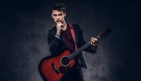 Όμορφος νέος στοχαστικός μουσικός με τη μοντέρνη τρίχα στα κομψά ενδύματα που θέτουν με μια κιθάρα στα χέρια του Στοκ φωτογραφία με δικαίωμα ελεύθερης χρήσης