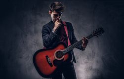Όμορφος νέος στοχαστικός μουσικός με τη μοντέρνη τρίχα στα κομψά ενδύματα που θέτουν με μια κιθάρα στα χέρια του Στοκ Φωτογραφίες