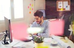 Όμορφος νέος χαμογελώντας επιχειρηματίας που εργάζεται με τα έγγραφα Στοκ Εικόνες