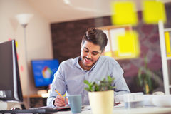 Όμορφος νέος χαμογελώντας επιχειρηματίας που εργάζεται με τα έγγραφα Στοκ Εικόνα