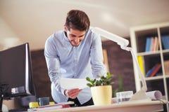 Όμορφος νέος χαμογελώντας επιχειρηματίας που εργάζεται με τα έγγραφα Στοκ Φωτογραφία