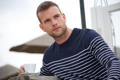 Όμορφος νεαρός άνδρας με τον καφέ του Στοκ Εικόνες