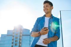 Όμορφος νεαρός άνδρας με το κινητό τηλέφωνο που ονειρεύεται υπαίθρια Στοκ Φωτογραφίες