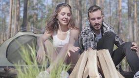 Όμορφος νεαρός άνδρας πορτρέτου που ανάβει μια πυρκαγιά στο δάσος ενώ λατρευτή νέα συνεδρίαση γυναικών πλησίον Στήριξη ζευγών αγά φιλμ μικρού μήκους
