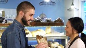 Όμορφος νεαρός άνδρας που αγοράζει το φρέσκο ψωμί από έναν θηλυκό αρτοποιό απόθεμα βίντεο