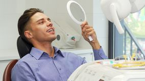 Όμορφος νεαρός άνδρας που εξετάζει τα δόντια του στον καθρέφτη στην οδοντική κλινική απόθεμα βίντεο