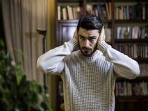 Όμορφος νεαρός άνδρας που καλύπτει τα αυτιά του, πάρα πολύς θόρυβος Στοκ Εικόνες