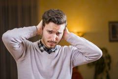 Όμορφος νεαρός άνδρας που καλύπτει τα αυτιά του, πάρα πολύς θόρυβος Στοκ φωτογραφίες με δικαίωμα ελεύθερης χρήσης