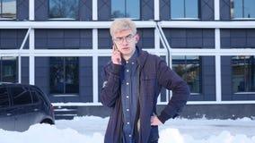 Όμορφος νεαρός άνδρας που μιλά σε έναν κινητό στην οδό της μεγάλης πόλης φιλμ μικρού μήκους