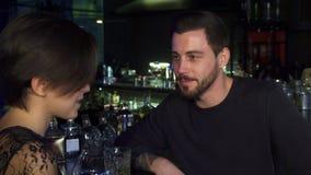 Όμορφος νεαρός άνδρας που μιλά στην όμορφη φίλη του στο φραγμό απόθεμα βίντεο