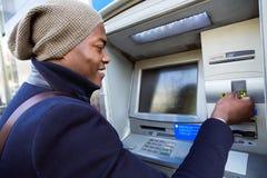 Όμορφος νεαρός άνδρας που παίρνει τα μετρητά από το ATM με την πιστωτική κάρτα Στοκ εικόνες με δικαίωμα ελεύθερης χρήσης
