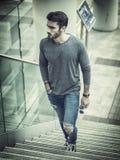 Όμορφος νεαρός άνδρας που περπατά στο κλιμακοστάσιο Στοκ Εικόνες
