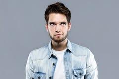 Όμορφος νεαρός άνδρας που σκέφτεται πέρα από το γκρίζο υπόβαθρο Στοκ Φωτογραφίες