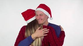 Όμορφος νεαρός άνδρας που φορά το καπέλο Χριστουγέννων που αγκαλιάζει τη φίλη του απόθεμα βίντεο