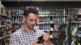 Όμορφος νεαρός άνδρας που χαμογελά στη κάμερα επιλέγοντας το κρασί φιλμ μικρού μήκους