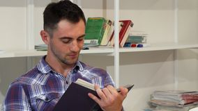 Όμορφος νεαρός άνδρας που χαμογελά χαρωπά διαβάζοντας ένα βιβλίο απόθεμα βίντεο