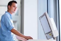 Όμορφος νεαρός άνδρας που χρησιμοποιεί μια μηχανή αντιγράφων Στοκ Εικόνες