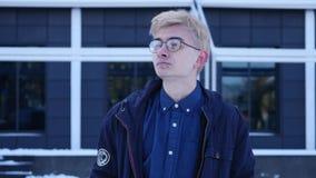 Όμορφος νεαρός άνδρας στα γυαλιά που παρουσιάζουν διαφορετικές συγκινήσεις απόθεμα βίντεο
