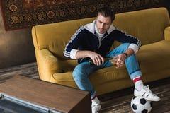 όμορφος νεαρός άνδρας στα εκλεκτής ποιότητας ενδύματα με το ποδόσφαιρο προσοχής σφαιρών στην παλαιά TV και τη χύνοντας μπύρα στοκ φωτογραφία