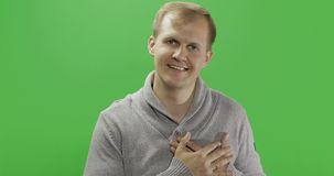 Όμορφος νεαρός άνδρας στο γκρίζο πουλόβερ που κάνει τη χειρονομία αγάπης E φιλμ μικρού μήκους