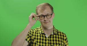 Όμορφος νεαρός άνδρας στο κίτρινο πουκάμισο που γυρίζει το κεφάλι του και που κοιτάζει στη κάμερα απόθεμα βίντεο