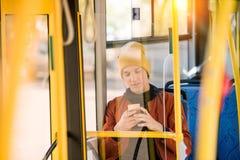 όμορφος νεαρός άνδρας στο καπέλο που χρησιμοποιεί το smartphone καθμένος Στοκ Εικόνες