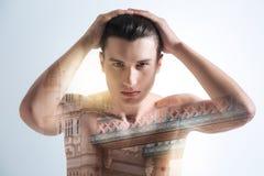 Όμορφος νεαρός άνδρας σχετικά με το κεφάλι του Στοκ φωτογραφία με δικαίωμα ελεύθερης χρήσης