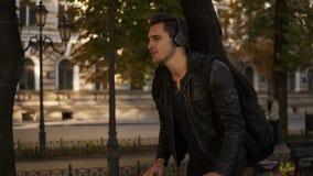 Όμορφος νεαρός άνδρας Brunette στα μαύρα περιστασιακά ενδύματα, ακουστικά που οδηγούν ένα ποδήλατο από το στρωμένο πάρκο πόλεων μ απόθεμα βίντεο