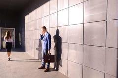 Όμορφος νεαρός άνδρας, επιχειρηματίας που μιλά στα τηλεφωνικά περάσματα από το beaut Στοκ εικόνα με δικαίωμα ελεύθερης χρήσης