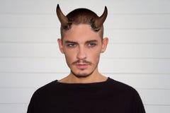 Όμορφος νεαρός άνδρας με τα κέρατα και τα μπλε μάτια αποκριών Στοκ Εικόνες