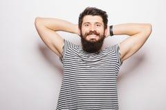 Όμορφος νεαρός άνδρας με τα χέρια εκμετάλλευσης γενειάδων πίσω από επικεφαλής και το χαμόγελο Στοκ Εικόνες