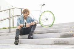 Όμορφος νεαρός άνδρας με το κινητό τηλέφωνο και το σταθερό ποδήλατο εργαλείων Στοκ Φωτογραφία
