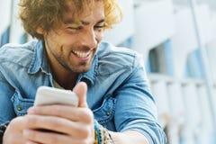 Όμορφος νεαρός άνδρας με το κινητό τηλέφωνο και το σταθερό ποδήλατο εργαλείων Στοκ εικόνες με δικαίωμα ελεύθερης χρήσης