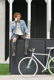Όμορφος νεαρός άνδρας με το κινητό τηλέφωνο και το σταθερό ποδήλατο εργαλείων Στοκ Εικόνες