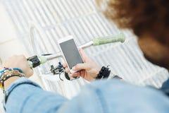 Όμορφος νεαρός άνδρας με το κινητό τηλέφωνο και το σταθερό ποδήλατο εργαλείων Στοκ φωτογραφίες με δικαίωμα ελεύθερης χρήσης