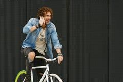 Όμορφος νεαρός άνδρας με το κινητό τηλέφωνο και το σταθερό ποδήλατο εργαλείων Στοκ Φωτογραφίες