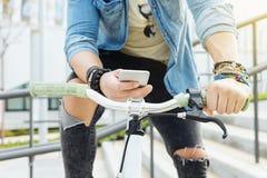 Όμορφος νεαρός άνδρας με το κινητό τηλέφωνο και το σταθερό ποδήλατο εργαλείων Στοκ φωτογραφία με δικαίωμα ελεύθερης χρήσης