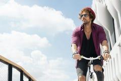 Όμορφος νεαρός άνδρας με το κινητό τηλέφωνο και το σταθερό ποδήλατο εργαλείων Στοκ εικόνα με δικαίωμα ελεύθερης χρήσης
