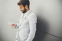 Όμορφος νεαρός άνδρας με το κινητό τηλέφωνο στο γραφείο Στοκ φωτογραφία με δικαίωμα ελεύθερης χρήσης