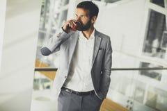 Όμορφος νεαρός άνδρας με το κινητό τηλέφωνο στο γραφείο Στοκ εικόνα με δικαίωμα ελεύθερης χρήσης