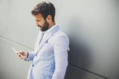 Όμορφος νεαρός άνδρας με το κινητό τηλέφωνο στο γραφείο Στοκ Εικόνες
