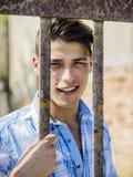 Όμορφος νεαρός άνδρας πίσω από τους φραγμούς κλουβιών μετάλλων Στοκ Φωτογραφίες