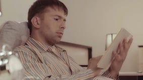 Όμορφος νεαρός άνδρας που βρίσκεται κάτω από το κάλυμμα και που κοιτάζει μέσω του βιβλίου απόθεμα βίντεο