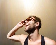 Όμορφος νεαρός άνδρας που γελά με τα γυαλιά ηλίου Στοκ Εικόνες